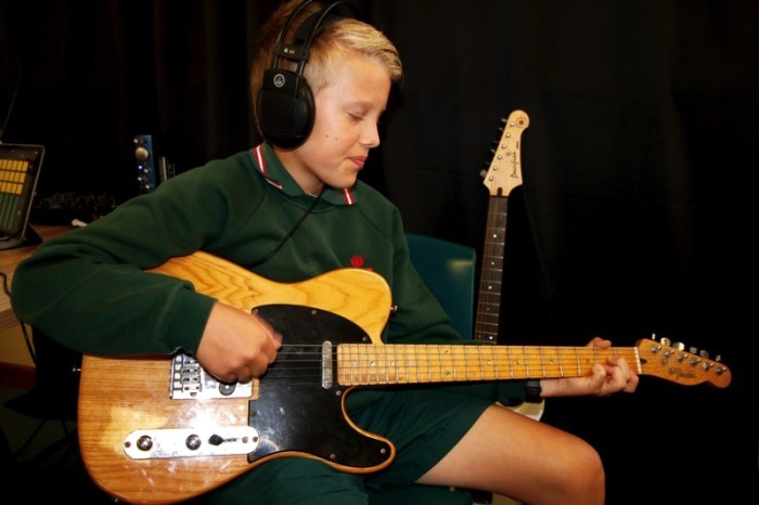 a student playing the guitar.